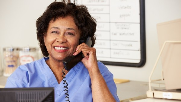 Smiling medical receptionist taking a phone call